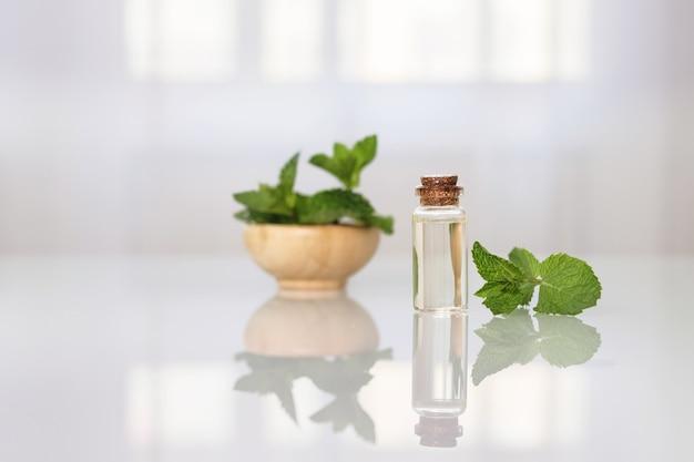 Huile essentielle de menthe dans une petite bouteille sur une table en verre.