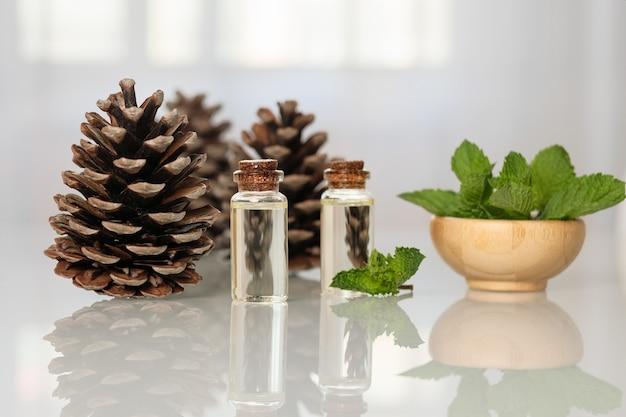 Huile essentielle de menthe et de pin dans de petites bouteilles sur une table en verre.