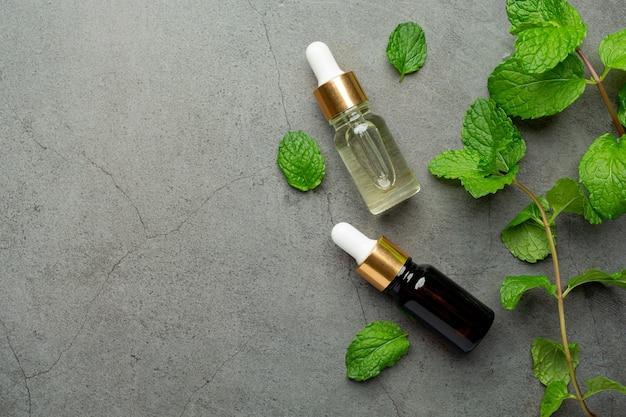 Huile essentielle de menthe poivrée en bouteille avec de la menthe verte fraîche