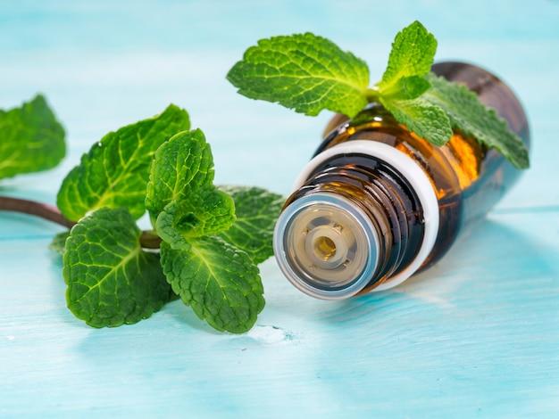 Huile essentielle de menthe poivrée dans une petite bouteille brune avec de la menthe verte fraîche sur fond en bois bleu. mise au point sélective, dof peu profond. copier l'espace