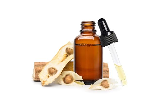 Huile essentielle de moringa en bouteille ambrée avec graines séchées et gousse isolé sur fond blanc.
