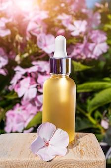 Huile essentielle naturelle dans un flacon en verre contre un espace de fleurs roses. le concept des essences bio, des cosmétiques naturels et des produits de santé. apothicaire moderne.