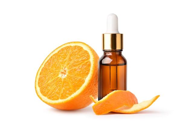 Huile essentielle d'orange dans un flacon compte-gouttes ambré avec fruits orange et écorce isolé sur blanc.