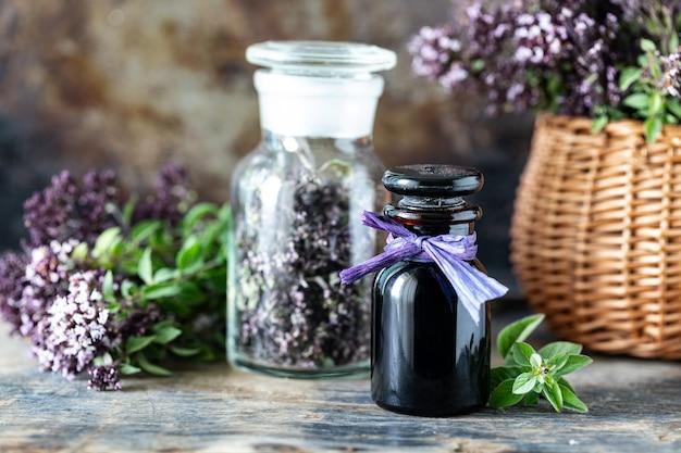 L'huile essentielle d'origan en bouteille en verre sur table en bois