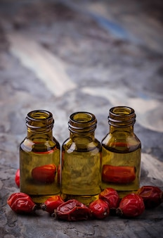 Huile essentielle de rose de chien sur de petites bouteilles. mise au point sélective
