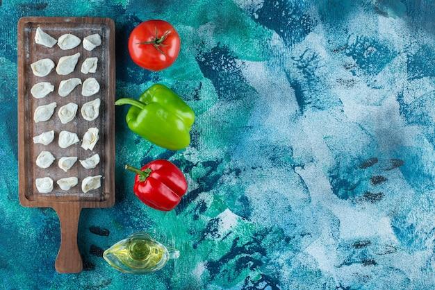 Huile et légumes à côté de raviolis turcs sur une planche , sur la table bleue.