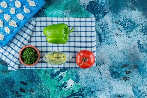 Huile et légumes à côté de raviolis turcs sur une planche sur le torchon, sur la table bleue.
