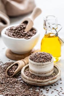 L'huile de lin dans une bouteille et un bol en céramique avec des graines de lin marron et une cuillère en bois. verticale