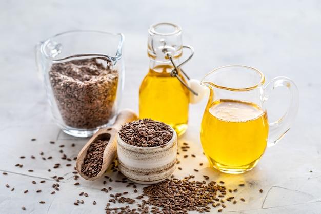 L'huile de lin dans une bouteille et un bol en céramique avec des graines de lin marron et une cuillère en bois