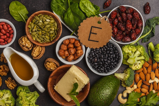 Huile, noix, avocat, beurre, graisses saines, églantier, persil, graines, épinards. fond sombre, vue de dessus