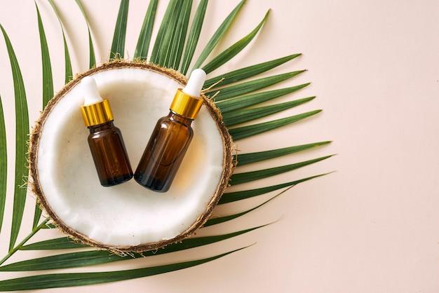 Huile de noix de coco en bouteille avec noix ouvertes et pulpe en pot, fond de feuille de palmier vert. produits cosmétiques naturels.