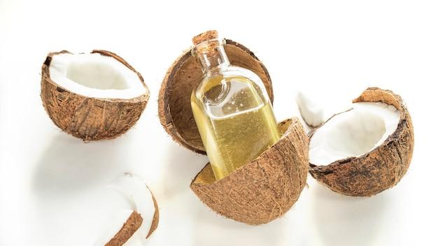 Huile de noix de coco dans une bouteille et noix de coco sur fond blanc produit de soins capillaires