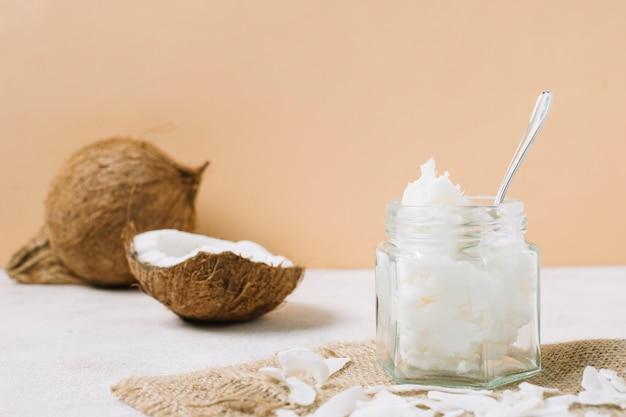Huile de noix de coco à faible angle de vue dans un bocal avec noix