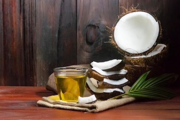 Huile de noix de coco avec des morceaux de noix de coco et noix de coco et feuille sur table en bois