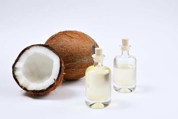 Huile de noix de coco naturelle en bouteilles sur blanc