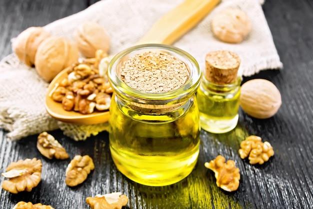 Huile de noix dans un pot et une bouteille, noix en cuillère et sur table, serviette en toile de jute sur fond de planche de bois