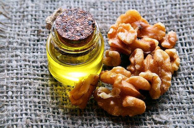 Huile de noix avec des noix pelées sur une toile de jute