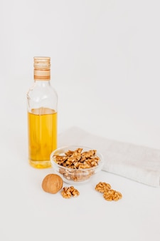 Huile de noix ou d'olive en verre de bouteille, gros noyau de noix pelé entier avec coque mince sur fond blanc. alimentation saine pour le cerveau. noix fraîches concept de noix de fond