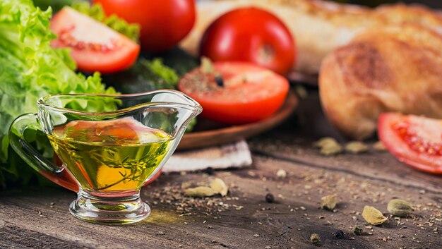 Huile d'olive aux herbes de thym sur table en bois rustique et légumes frais pour cuisiner la salade. fond de nourriture saine.