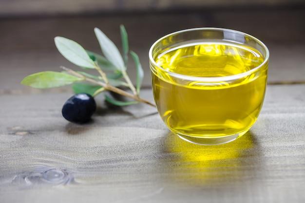 Huile d'olive et branche d'olive sur le fond en bois, huile d'olive des pouilles, gros plan