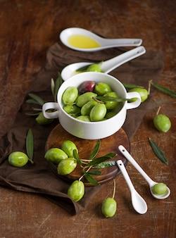 Huile d'olive et branche d'olivier sur fond noir.