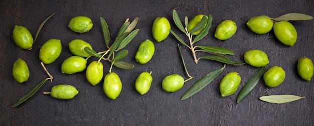 Huile d'olive et branche d'olivier sur la surface noire
