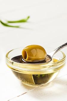 L'huile d'olive et la branche d'olivier sur la table en bois