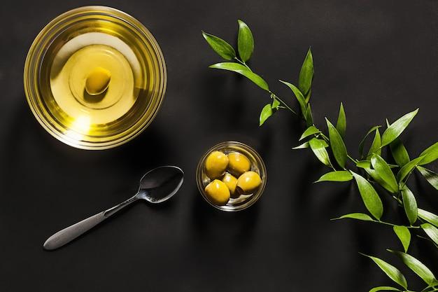 Huile d'olive et branche d'olivier sur la table en bois