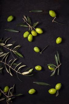 Huile d'olive et branche d'olivier sur la table noire.