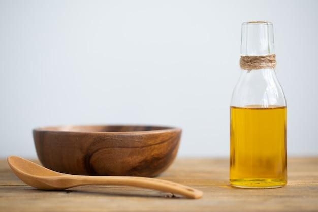 Huile d'olive dans une bouteille, une cuillère, une assiette sur une table en bois sur fond blanc. espace de copie.