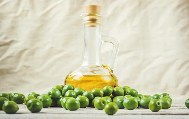L'huile d'olive dans une bouteille transparente sur un fond en bois. mise au point sélective.
