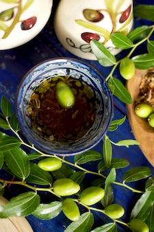 L'huile d'olive dans la tasse. branche d'un olivier avec des olives fraîches. olives vertes. dans le jardin. sur une planche de bois. une cruche d'huile. classiques italiens. olives d'italie. nourriture d'italie