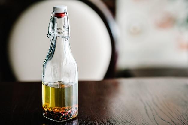 L'huile d'olive avec différentes épices dans un bon bocal en verre transparent sur un bureau en bois brun