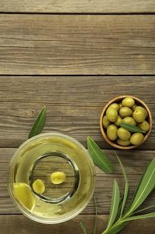 Huile d'olive à l'olive sur fond gris avec espace de copie. photo verticale