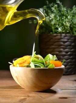 L'huile d'olive tombant sur deux olives à feuilles d'olivier pour assaisonner une salade méditerranéenne.