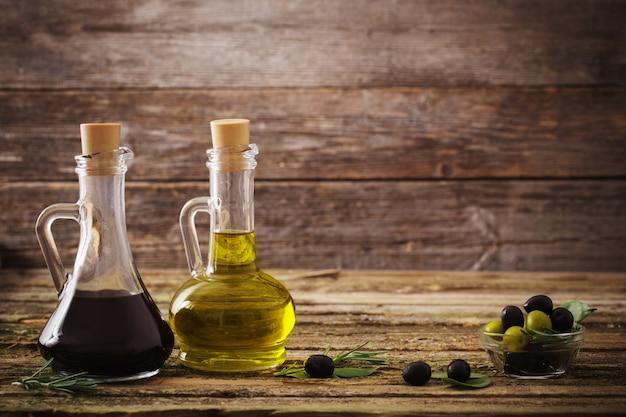 L'huile d'olive et le vinaigre balsamique sur un fond en bois