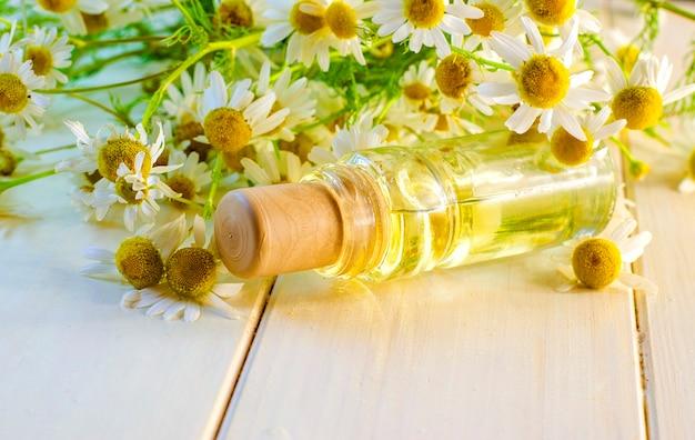Huile parfumée de fleurs de camomille dans une bouteille en verre