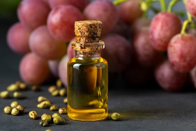 Huile de pépins de raisin dans un bocal en verre et raisins frais