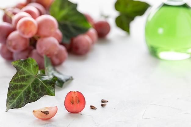 Huile de pépins de raisin dans une bouteille en verre avec une grappe de raisin.