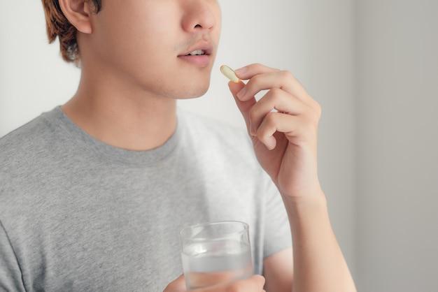 L'huile de poisson est mangée par un homme dans les mains de flacons et d'une bouteille en verre pilule homme nutrition pharmacie soins nutritionnels du foie,