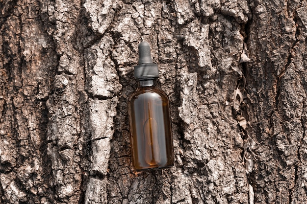 Huile de sérum dans une bouteille cosmétique en verre ambré sur l'écorce d'arbre vue de dessus sérum anti-vieillissement avec collagène et