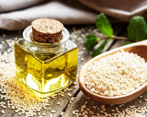 L'huile de sésame et les graines sur une table rustique.