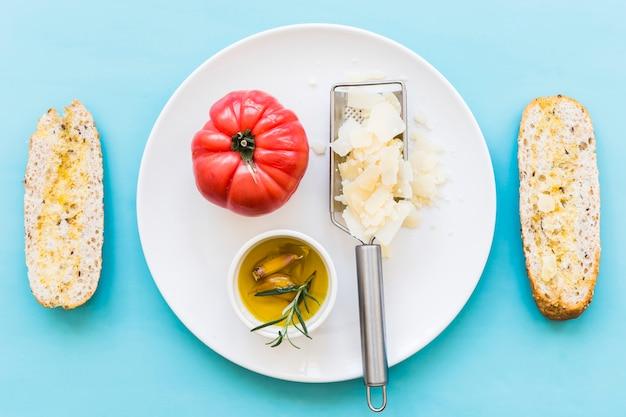Huile avec tomate et fromage râpé sur plaque avec deux tranches de pain sur le fond bleu