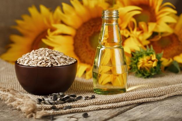 L'huile de tournesol dans une bouteille en verre avec des graines dans une tasse et des fleurs sur une table en bois.