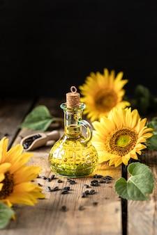 Huile de tournesol dans une bouteille en verre avec graines et fleurs de tournesol