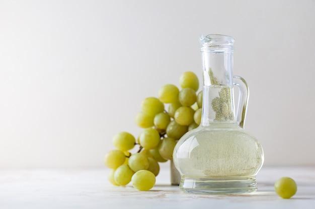 Huile végétale biologique de pépins de raisin dans une bouteille en verre avec des raisins verts