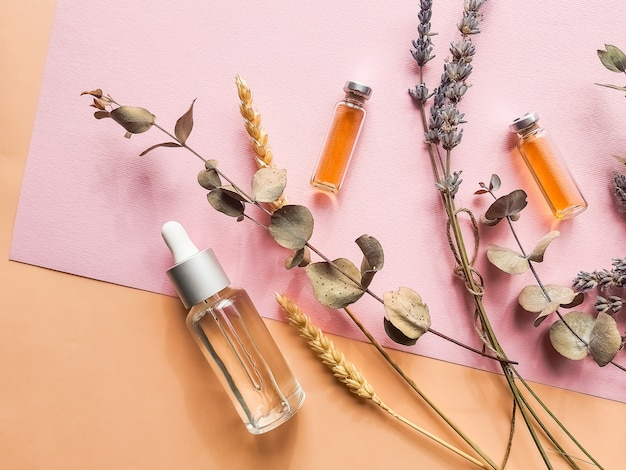 Huile végétale et fleurs de lavande sur mur pastel. bouteille d'huile essentielle avec de la lavande.cosmétiques naturels avec de la lavande et de l'orange, du citron pour un spa fait maison
