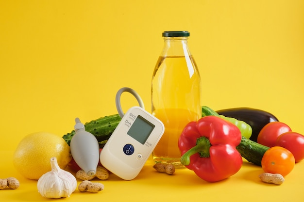 Huile végétale, légumes et tensiomètre sur fond jaune. nutrition et régime alimentaire pour l'hypertension artérielle et les maladies cardiaques