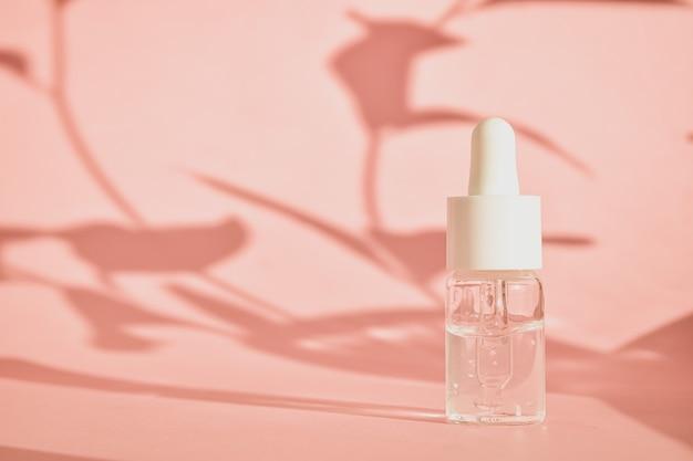 Huiles aromatiques cosmétiques en bouteilles avec une pipette sur rose