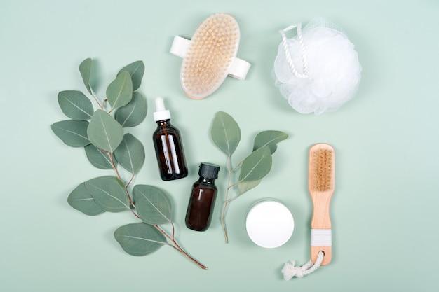 Huiles essentielles, contenant de crème pour le visage et brosses de massage avec des feuilles d'eucalyptus naturelles sur fond vert